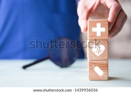 Doctor hand arranging wood block stacking with icon healthcare and medical, insurance for your health search.