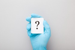 Doctor hand in blue rubber protective glove showing question mark. Gray background. Concept of medical issues. Closeup.