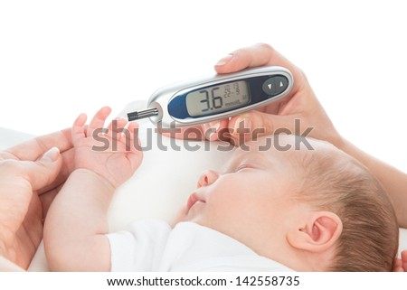 Doctor hand measuring glucose level blood test from diabetes patient child baby using glucometer and small drop of blood from finger and test strips isolated on a white background