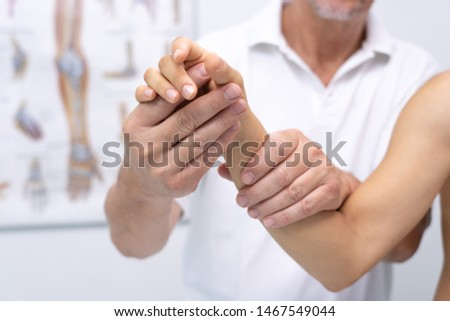 Doctor hand Physicist physical therapy treatment patient in the clinic. Orthopedic medical exam in doctor's hospital office Partnership, traumatology and medical consultation for hand wrist injury