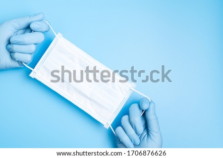 Doctor hand wear blue medical gloves holds antivirus face mask on blue background for pandemic, airborne diseases, outbreak, Covid19 concept
