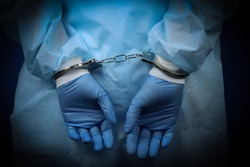 Doctor handcuffed, hands close-up, concept of medical corruption, bribery, crime