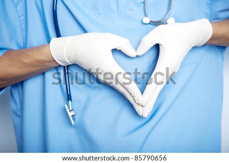 Doctor hands in gloves in the shape against the background of his body. closeup