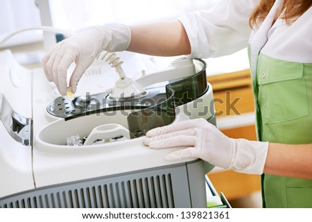 Doctor hands in medical gloves with clinical dna chemistry samples near equipment for medical tests