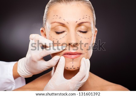 doctor hands on mid age woman before cosmetic surgery