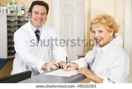 Doctor helps senior patient with her medical forms.