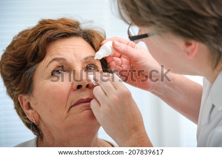 Doctor helps the patient and gives the eye drops