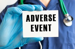Doctor holding a card with text ADVERSE EVENT. Medical concept.