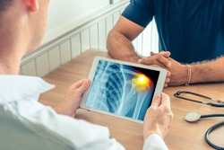 Doctor holding a digital tablet with x-ray of the chest of the patient with pain on the shoulder