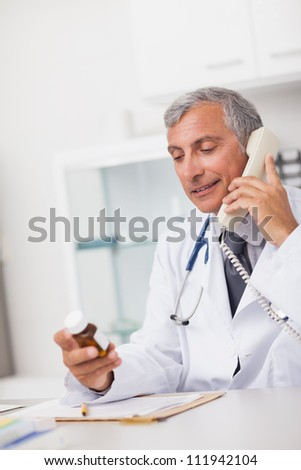 Doctor holding a drug box and a phone in a medical office