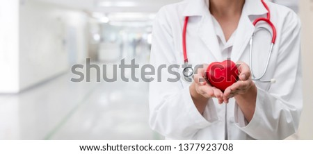 Doctor holding a red heart at hospital office. Medical health care and doctor staff service concept. Foto stock ©