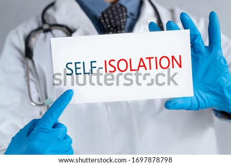 """Doctor holding a sign saying """"Doctor holding a sign saying """"Self-isolation"""" global message for the coronavirus crisis. Quarantine message across the globe to fight COVID-19 pandemic."""