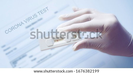 Doctor holding a test kit for viral disease COVID-19 2019-nCoV. Lab card kit test for viral novel coronavirus. Negative test result by using rapid test device for COVID-19.