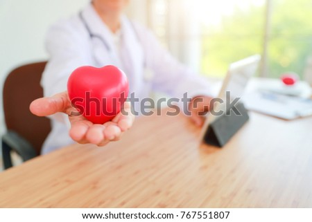 doctor holding and giving a red heart of love and care concept (medical concept) #767551807