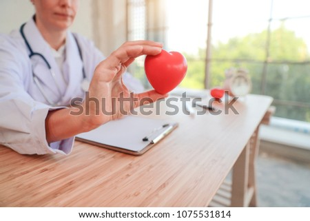 doctor holding and giving a red heart of love and care (this image for medical concept) #1075531814