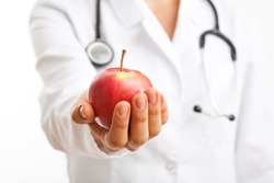 Doctor holding apple and recommending healthy lifestyle