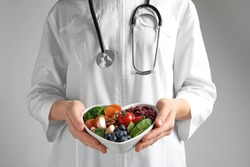 Doctor holding bowl with products for heart-healthy diet on color background, closeup