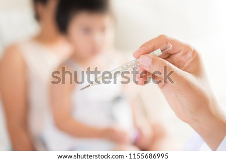 Doctor holding digital thermometer to measuring temperature of her ill kid and sick little girl with mother in background.