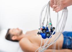 Doctor holding ECG electrodes for heart diagnostic over mature man. Medical equipment for electrocardiogram close up