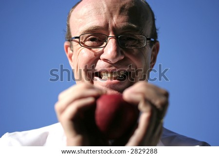 Doctor holding juicy red apple in both hands and smiling, showing head, hands, apple , doctors laboratory coat and a beautiful blue sky in the background