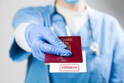 Doctor holding passport with COVID-19 sign stamped onto white paper,immunity passport risk-free certificate concept,recovered Coronavirus COVID19 patients being issued proof of convalescence,UK ID