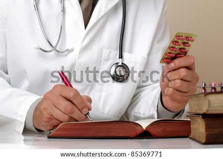 Doctor holding pills writing patient notes on a medical examination form or prescription