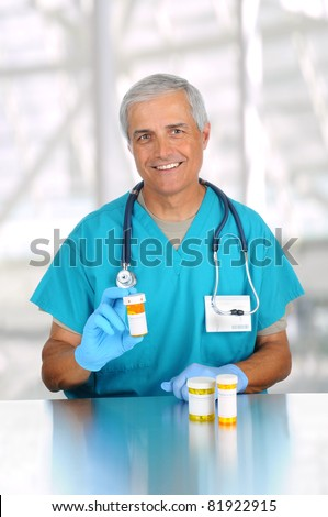 Doctor holding prescription medicine bottle in modern medical facility. Man is wearing scrubs and stethoscope. Vertical format.