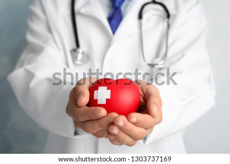 Doctor holding red heart with adhesive plasters, closeup view. Cardiology concept #1303737169