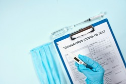 Doctor holding thermometer over the coronavirus test form. Getting the COVID-19 test. Testing for 2019-ncov. Medical test form for new corona virus with medical supplies and equipment