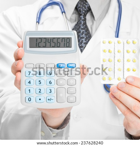 Doctor holdling calculator and pills in his hands - medical aid concept