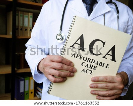 Doctor holds a book Affordable care act ACA. Imagine de stoc ©