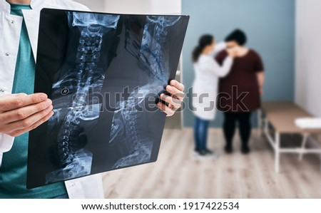 Doctor holds an x-ray of a cervical spine over background osteopath check-up overweight woman's spine. Scoliosis of spine, diagnosis
