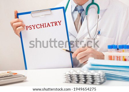 Doctor holds paper with inscription - PSYCHIATRY, stethoscope and pills on table Сток-фото ©