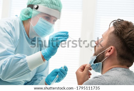 Doctor in a protective suit taking a throat and nasal swab from a patient to test for possible coronavirus infection Photo stock ©