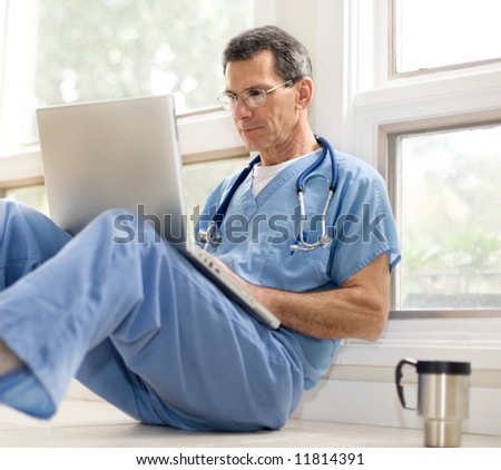 Doctor in blue scrubs relaxing with his laptop on coffee break. Selective focus.