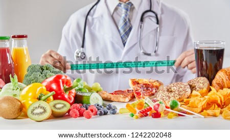 Doctor in coat with long stethoscope holding ruler over table with random assortment of healthy and unhealthy food #1242202048