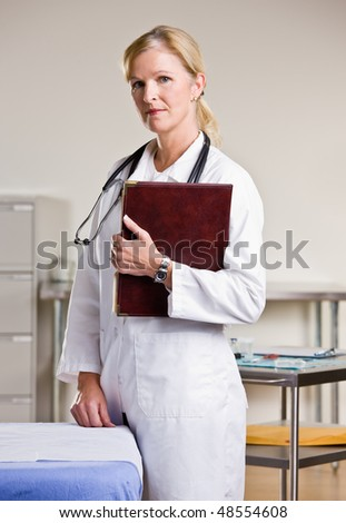 Doctor in doctor office holding notebook