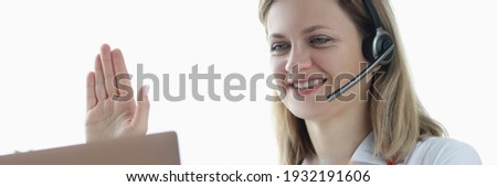 Doctor in headphones with microphone waving his hand at laptop screen. Medical videoconference concept