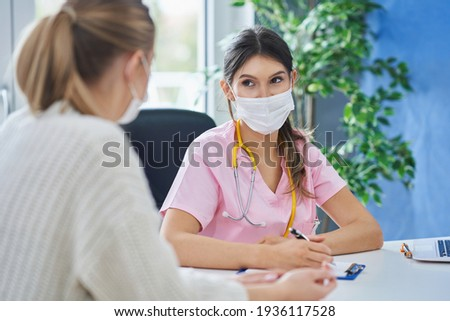 Doctor in mask explaining diagnosis to her female patient Stockfoto ©