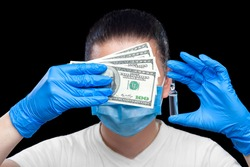 doctor in medical mask and sterile gloves holds glass ampoule with virus vaccine and cash covering his face with bribe, faceless portrait concept on theme of medicine and expensive pharmaceuticals.