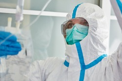 Doctor in protective clothing in hospital intensive care unit treats Covid-19 patient with infusion during coronavirus pandemic