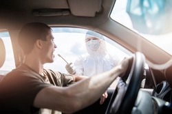 Doctor in protective virus suit taking swab from person driver to test for COVID-19 coronavirus infection.