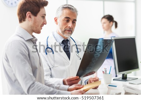Doctor in the office examining an x-ray and discussing with a patient