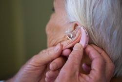 Doctor inserting hearing aid in senior patient ear in hospital
