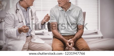 Doctor interacting with senior patient in clinic