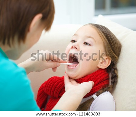 Doctor is examining a little girl, indoor shoot