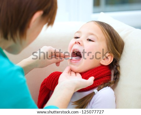 Doctor is examining a little girl, indoor shoot - stock photo