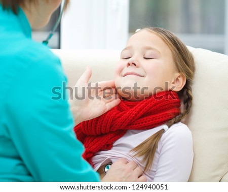 Doctor is examining little girl, indoor shoot