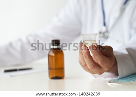 Doctor is giving a medicine in the consulting room. There is a cup with cough syrup in his hand.