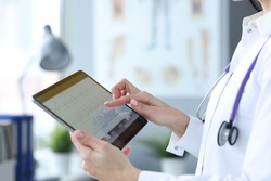 Doctor is holding tablet with heart cardiogram. Examination of cardiovascular system concept